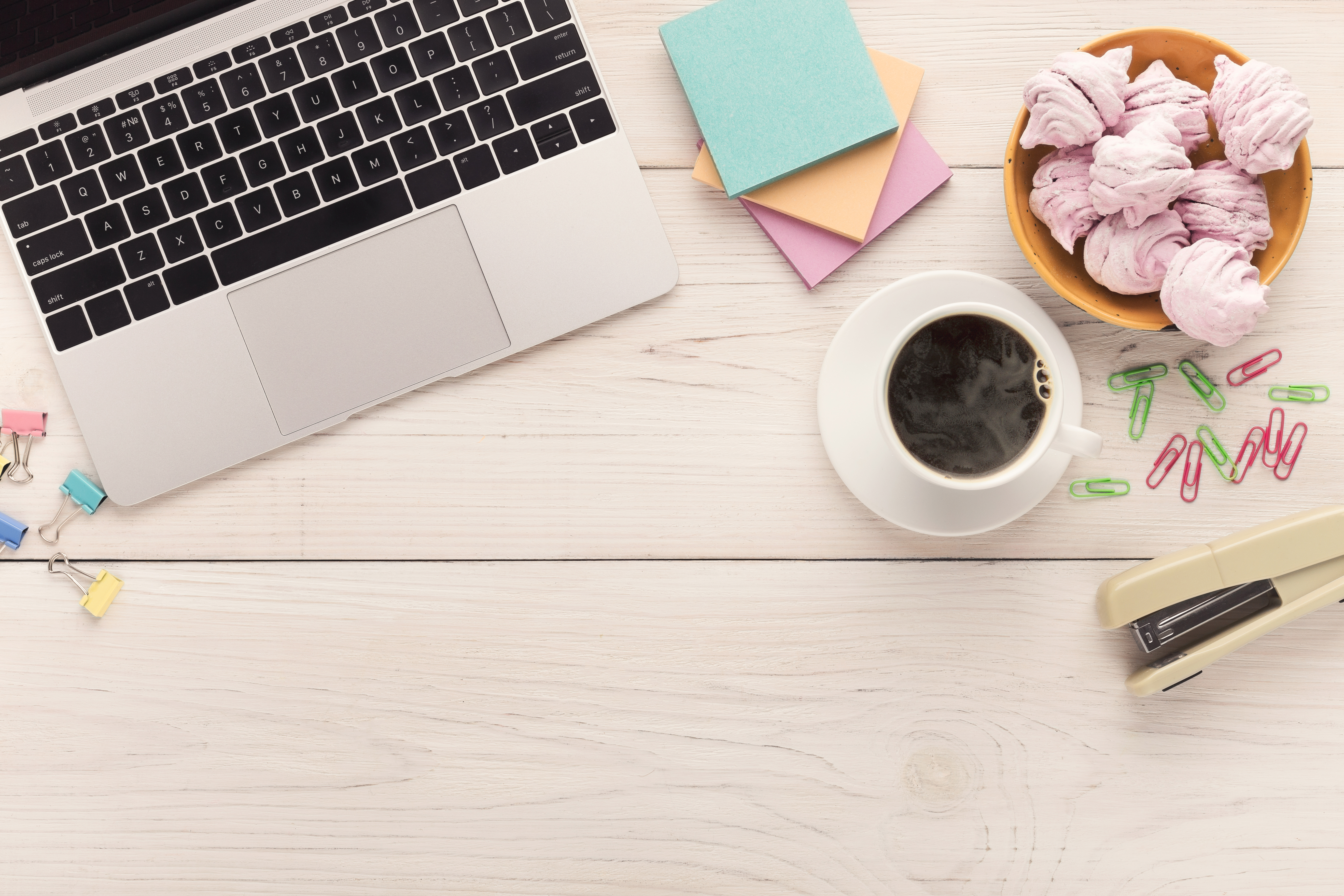 Desk with coffe cup, laptop keyboard, sweets and stationery on white background, copy space, top view. Girlish workplace, lifestyle concept